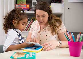 Speech therapist and Aboriginal girl reading a book