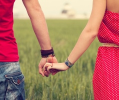 Couple holding hands in field.